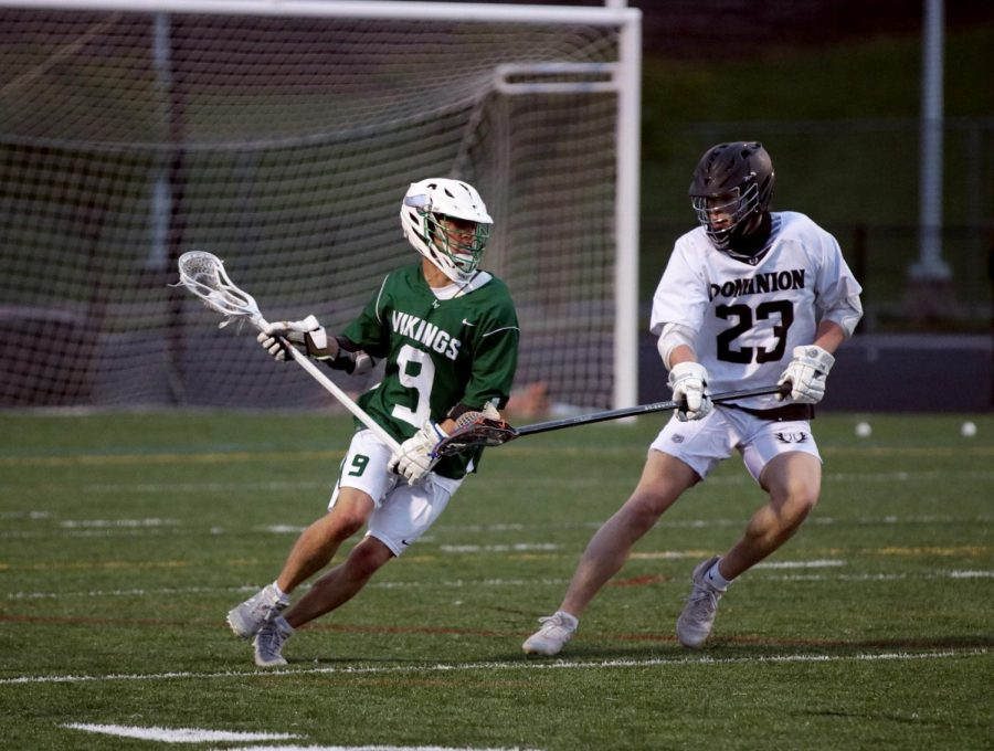 Midfielder Ryan Adams, takes on a Dominion defender, as he tries to help his team score a goal in the first quarter.