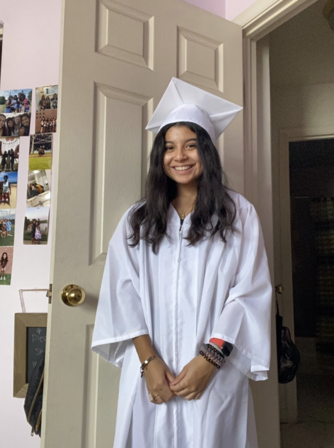 Senior Izzy Gracias, poses in her cap and gown as she nears the end of the nine weeks of high school and prepares to graduate with the class of 2021.