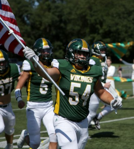 Cam Miller, senior defensive tackle, runs out on the field, holding an American flag.