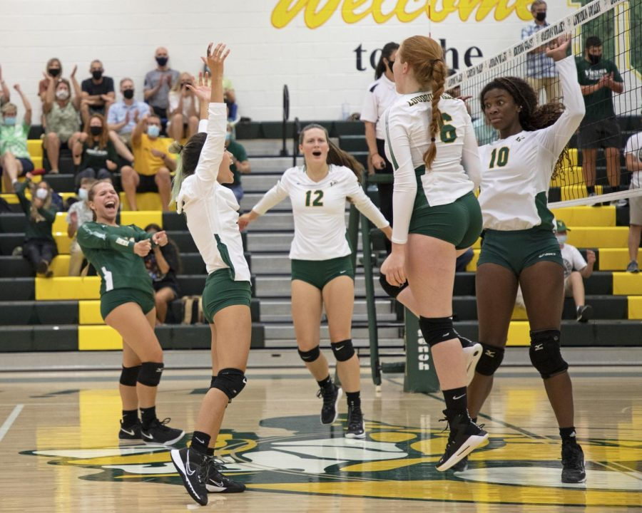 The girls varsity volleyball team celebrates on the court during a game. From left: Carly Zimmet, Becca Nyugen, Ashlyn Wade, Ellie Vest, Lara Moore.